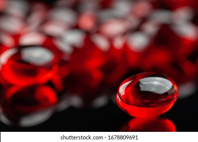 Close up of red gel capsule on black background