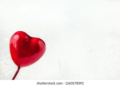 Close up of red glossy heart on blurred white background with copy space. Symbol of love and Valentine's day