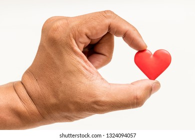 close up of red heart in hand isolated white background.