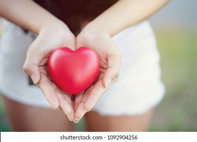 Close up of a red heart on a woman hand. It shows a love that is full of happiness. The combination of love of two people. To bring love together is a good thing to the whole world.