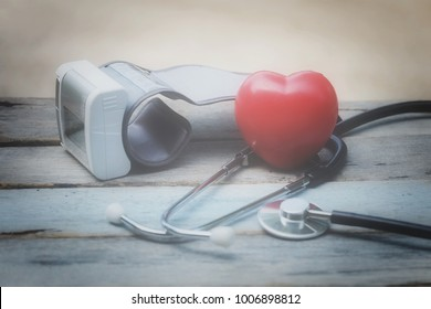 close up red heart, stethoscope and blood pressure monitor on old wood table, healthcare technology and world health day concept, vitage tone