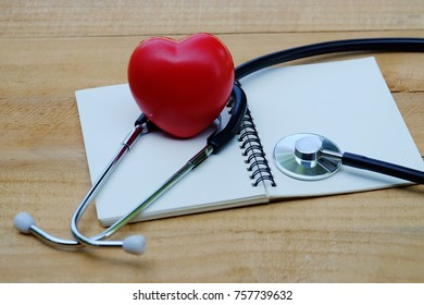 close up red heart, stethoscope and notebook on old wood table, world health day and business concept
