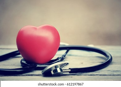 close up red heart and stethoscope on wood table, world health day concept, process vintage tone