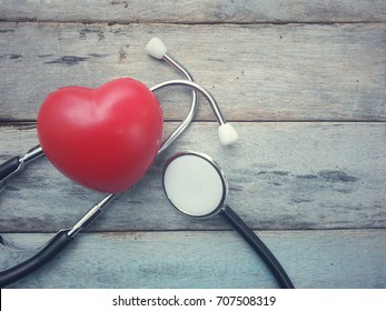 close up red heart and stethoscope on old wood table with copy space background, world health day and healthcare concept, process vintage tone