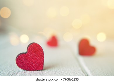 Close up of red hearts on wooden table against defocused lights. St. Valentine's Day background