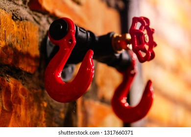 Close up red huge big hooks hanger or rack for clothing on brick stony wall in cafe bar pub cloakroom. Steampunk style design element