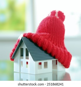 Close up Red Knitted bobble hat on Top of Cute Little House Placed on the Table.