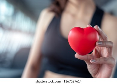 Close up of red massage ball like heart shape in fitness woman hand at sport gym training center. Medical and healthcare of heart attack and serious illness concept. Female sporty girl wear sport bra.
