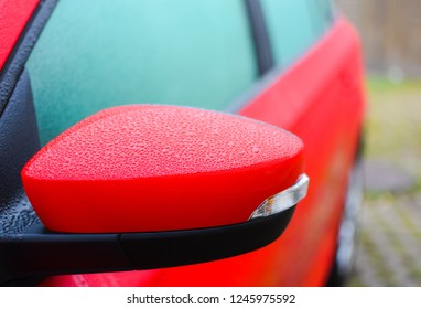 close up red mirrow of car with rain drop