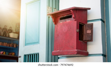 Close up of red old vintage wooden mailbox in front of vintage store. Red Asia wooden mail box on wooden vintage wall.