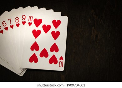 A close up of red playing cards on a dark wooden background.