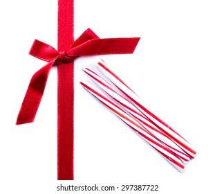 close up of a red ribbon and bow with peppermint stripped candy