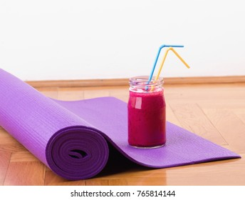 Close up of red smoothie in jar on purple mat on parquet floor. Wellbeing, sport and healthy lifestyle concept