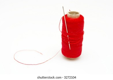 close up of red thread bobbin and needle
