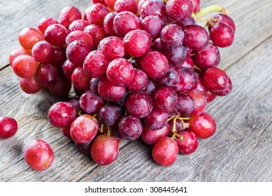 Close up of red, wet grapes  on a wood.