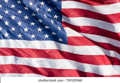 Close up of a red, white and blue American flag with wavy stars and stripes.
