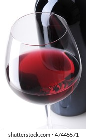 Close up of a Red Wine Bottle with wineglass in front, vertical format over white background