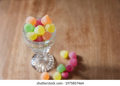 Close up red, yellow, green, orange liquor sweets gathered in a glass on a wooden table