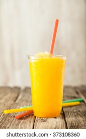 Close Up of Refreshing and Cool Bright Orange Slush Drink in Plastic Cup Served on Rustic Wooden Table with Collection of Colorful Drinking Straws