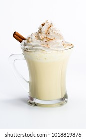 close up of a refreshing and sweet holiday treat, eggnog with whipped cream and cinnamon isolated on a white background