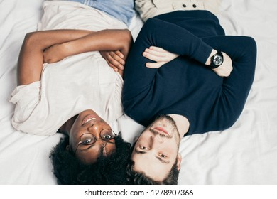 Close relationships, couple of young european guy and african girl lying together in bed, upside down view from above