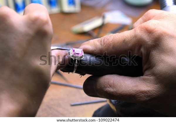 Close up of repairing ring set with Amethyst stone on wood stick tool