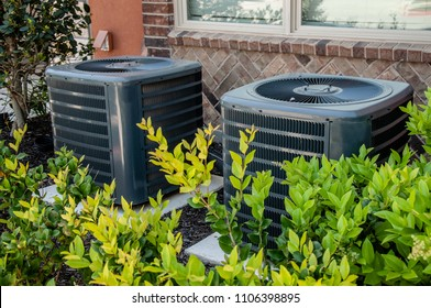 Close up  residential Air conditioner units outdoor red brick  bushes background