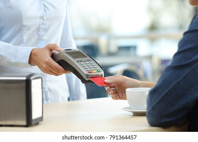 Close up of a restaurant customer hand paying with credit card