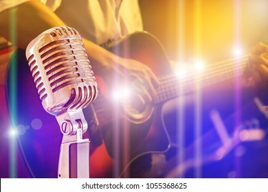 Close up retro microphone with musician playing acoustic guitar on band in night concert background