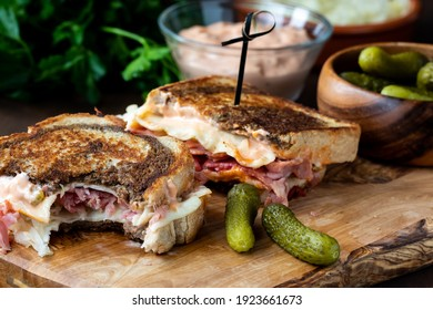 Close up of a Reuben sandwiches with a bite taken out of one, served with pickles and Russian dressing.