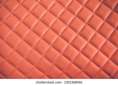 Close up of rhombus pattern with red stitch lines on red leather car seat upholstery background