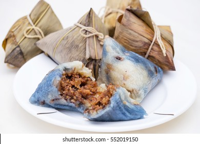 Close up of rice dumplings on white plate over white background.