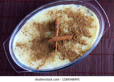 close up rice pudding with cinnamon in glass bowl on bamboo tablecloth