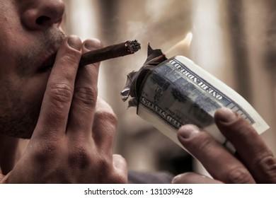 Close up rich brutal businessman lighting cigar with $100 US Dollar bill