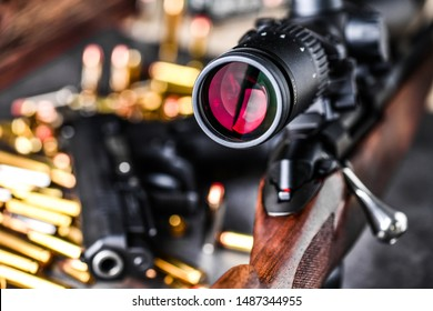 Close up of rifle scope hunting on wooden ammonition background. Hunt sniper gun, optics scopes close up.