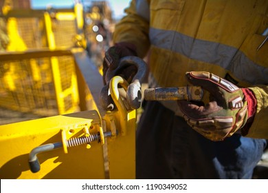 Close up rigger high risk worker wearing heavy duty glove, fastening industry pin into bow- shape shackle on crane lifting lug at construction site Perth city, Australia