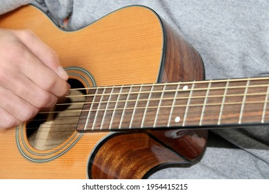 Close up of a Right Hand Strumming on a Steel String Acoustic Guitar