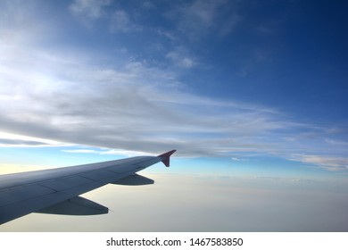 Close up of the right wings of an airplane, aeroplane, aircraft flying in the evening with blue sky and some scattered clouds, cumulus humilis, simpsons clouds hiding the sun, selective focusing