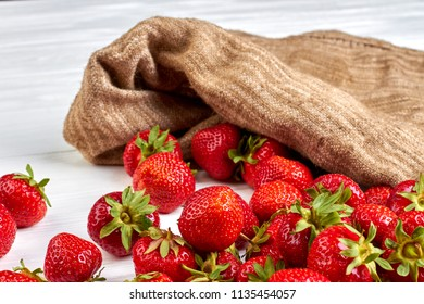 Close up ripe strawberries and burlap. Ripe organic strawberries and sack cloth. Wholesome seasonal fruit.