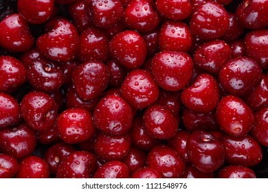 Close up of ripe sweet cherries pile. Large collection of fresh red cherries. Ripe cherries background.