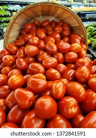 close up of ripe tomatoes spilling out of wooden bushel basket in the produce department