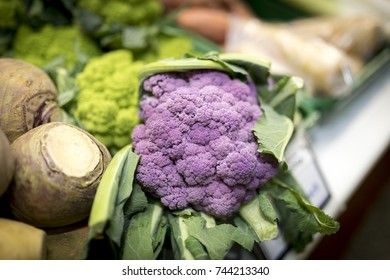 Close up of ripe and vibrant green Romanesco vegetables behind purple cauliflowers and swedes and on a market stall in Yorkshire,  UK