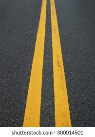 Close up road divide yellow twin line
