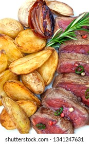 Close up of roast beef fried potatoes and shallots on a plate