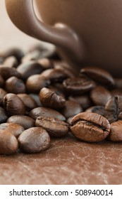 Close up roasted coffee beans and coffee cup