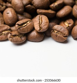Close up of roasted coffee beans heap. coffee beans on the white background