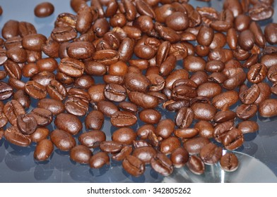 close up of roasted coffee beans on blurry background