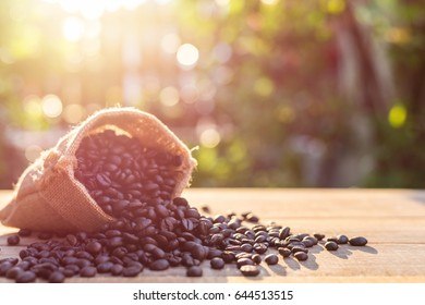 Close up roasted coffee beans in small sack on wooden table. Outdoor shooting with sunlight and blur background