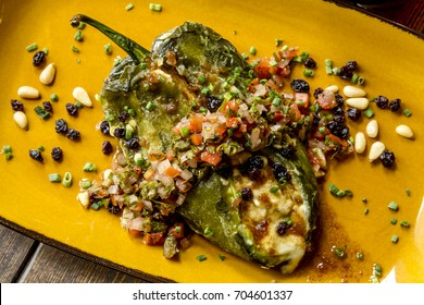 Close up of roasted Poblano pepper stuffed with melted cheese with fresh salsa garnish shot from above