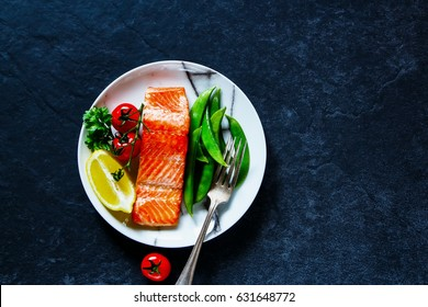 Close up of roasted salmon fillet with poached green peas, tomatoes and lemon in plate for protein rich dinner on dark vintage stone background, top view. Diet, healthy, clean eating concept